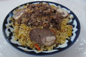 Plov adorned with kazy (horse meat sausage)