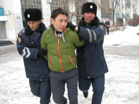 A protestor is bundled away by the police in Almaty