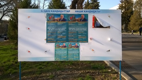 An election information board in downtown Almaty, Kazakhstan with a poster for the Leader and the communist candidate